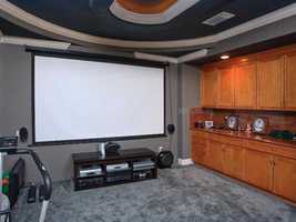 The home theater has a private balcony, an 8 foot overhead projection screen, a large wet bar and tiered leather chairs.