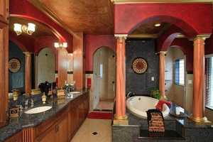 The master bathroom has a water closet with a private sink, a walk-in shower, jetted tub and crystal chandelier.