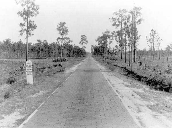 "An early brick ""highway"" near Orlando in 1917.  Officials say the white highway markers pictured on the left also functioned as billboards for local businesses."