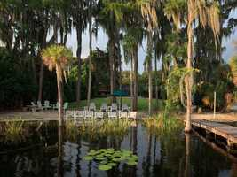 The huge backyard leads to the 85 feet of lakefront with sandy beach amongst the many Cypress trees.