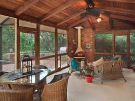 The warm and cozy back porch features a floor to ceiling wood burning stove, wooden ceiling with beams and easy access to the pool and brick paver patio.