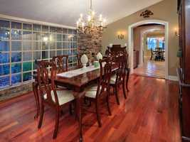 Entertaining is a delight with the beautiful butlers pantry wine bar and dining room featuring wood flooring and a brick accent wall.