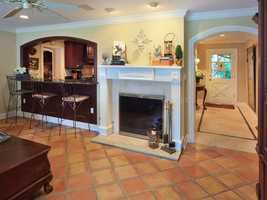The family room features a custom fireplace and bar seating.