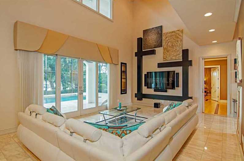 Off the kitchen is a family room w/ soaring ceilings, marble covered floor, and access to the the pool