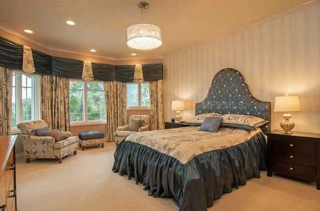This bedroom offers panoramic views of the pool and lake.