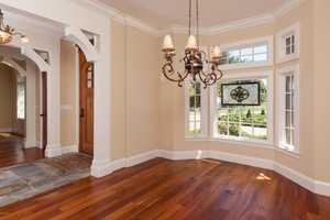 Make an immediate left into what could serve as a formal dining room. The room features hardwood floors, great views, and a glamorous chandelier.