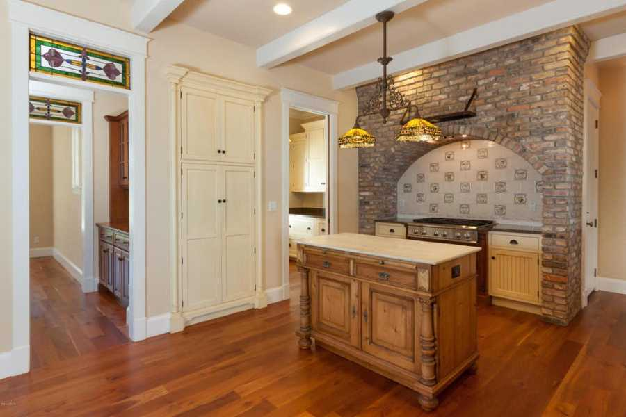 The interior has a bit of French Country charm with the antique brick arch over the stove, hand painted tiles & stained glass transoms.
