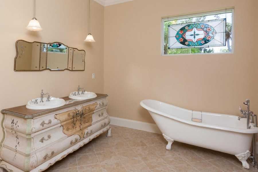 Luxurious master bath takes on an antique interior design.