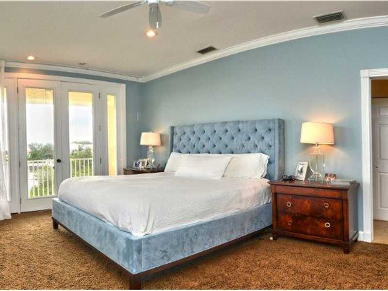Master bedroom features soft carpeting and a private balcony.