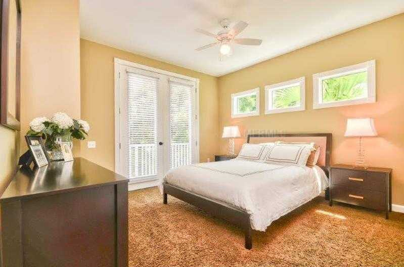 This guest bedroom features french double doors and three windows.