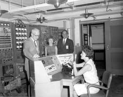 Two men and two women at work in mission control.  Photograph taken in 1967.