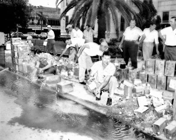 1956: Moonshine being dumped down a public drain in Polk County.
