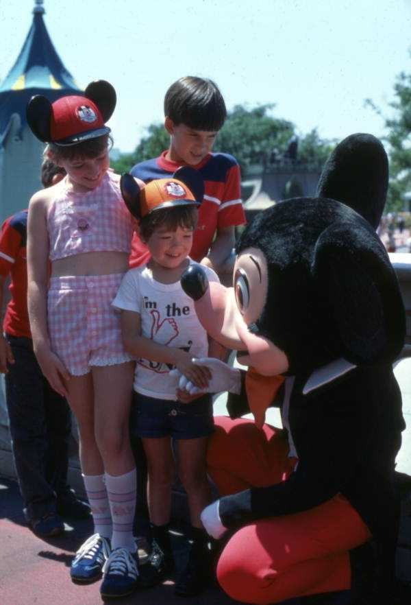 1977: Mickey Mouse with more park guests.