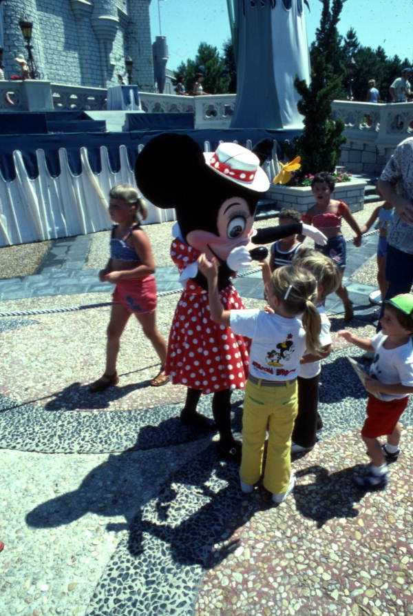 1977: Minnie Mouse donning a hat, greets guests outside of Cinderella's castle.