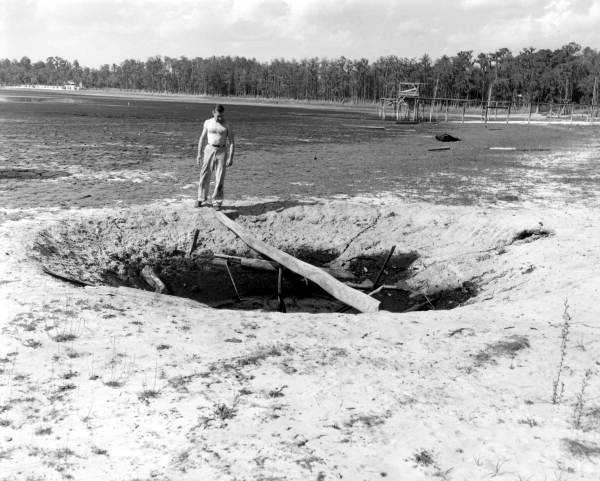 George Grose standing at sinkhole by a dried up Lake Bradford in 1955.