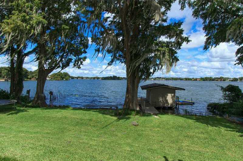 Enjoy boating on the largest lake on the Winter Park Chain from your dock featuring a storage room, 2 floating docks & electric hoist & remote controlled boat cover.