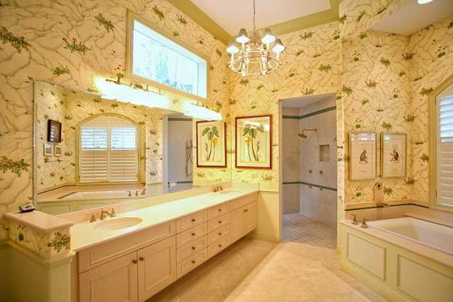 The master bathroom features dual vanity sinks and an elongated spa tub.