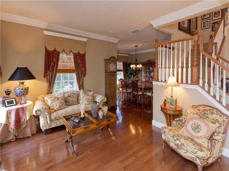 Three-tier crown molding, custom window treatments, and hardwood floors are featured throughout the home.