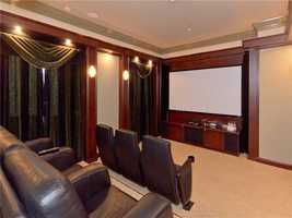 The upstairs loft entertainment space offers a custom bar & home theater with custom seating.