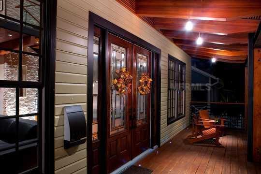 Visitors are greeted w/ a 35' wide stone porch flanked w/ gas lanterns.