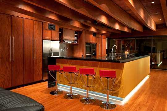 The mustard painted islands and red accent stools compliment the hardwood floors perfectly.
