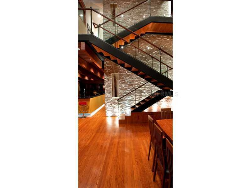 The stone wall provides a backdrop for the steel and glass floating staircase.
