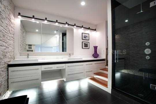 The black and white theme is amped up a notch in the bathroom, which features a white stone backsplash and darkly tinted glass shower doors.