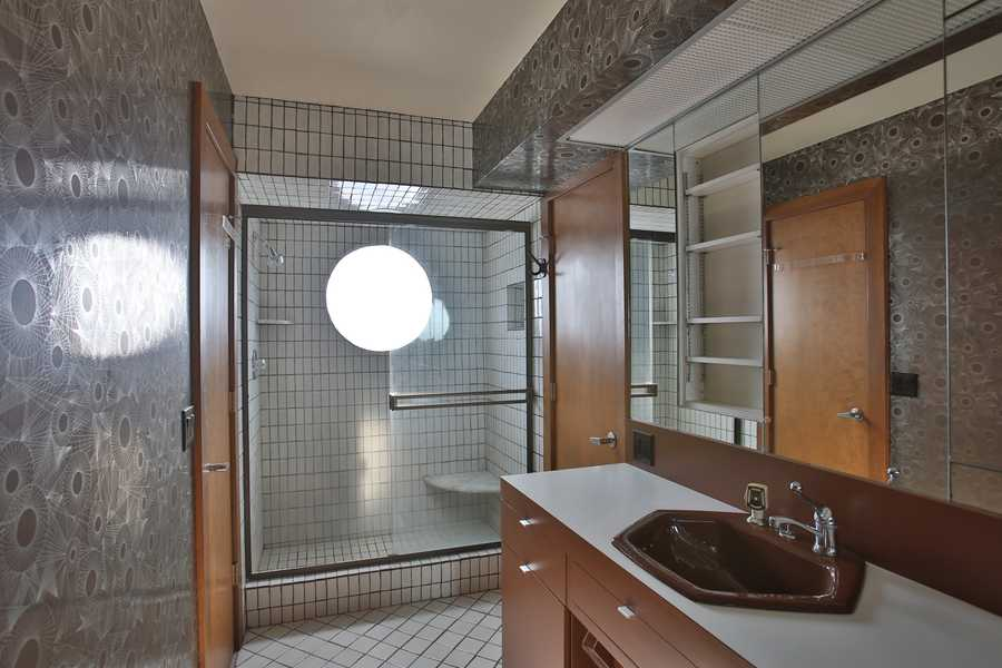 The shower in this guest bathroom features a petite bench.