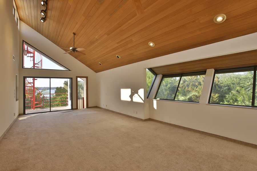 The master bedroom measures at 28 x 15 ft and looks out over the spectacular river view. It also features a winding staircase to an upper-level balcony and cedar wood ceiling.