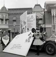Happy and Minnie Mouse continue with the parade with gigantic birthday cards addressed to Mickey Mouse.