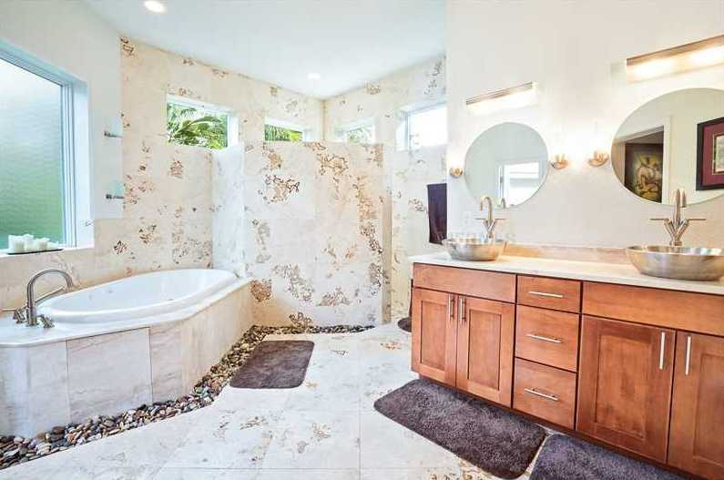 Natural materials beautify the en suite bathroom, which features dual vanity sinks, river stones around the spa tub and a separate shower.