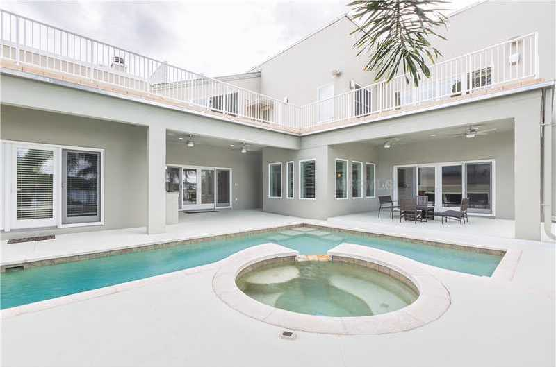 The expansive L-shape lap pool offers easy access into the warm jacuzzi.