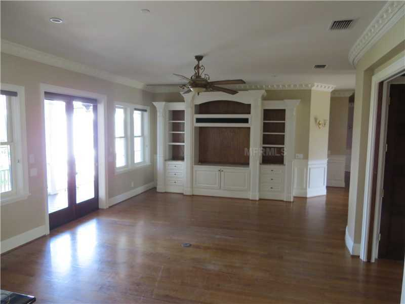 The family room features a custom entertainment unit, beautiful French doors, and hardwood floors.