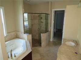 The en-suite bathroom features a luxurious spa-tub.