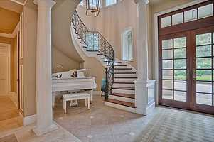 Inside, a grand entrance and elegant, spiral staircase immediately welcomes you upon entering the foyer of this two-story French country estate.
