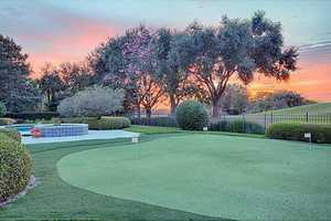 A one-of-a-kind putting green is between the beautiful pool and the famous Isleworth golf course.