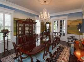 The formal dining room features a complete mural and seating for eight.