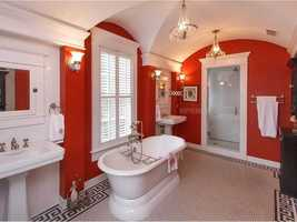 The grand bathroom has hexagon tile and a garden tub with views of the lake.