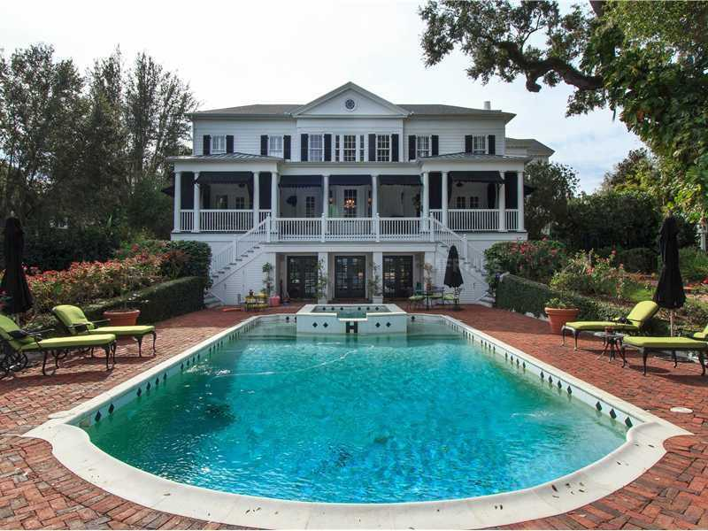 French doors and dual-sided stairs lead out to the pool.