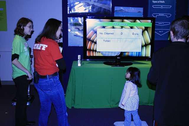 Audiences enjoy a virtual reality video game.