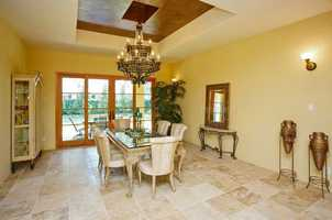Elegant dining room with tray ceiling and wood doors overlooking the sunny patio and backyard.