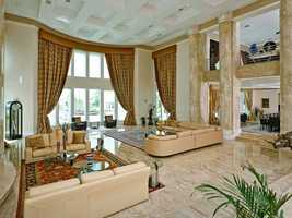 The formal living room features tall ceilings and floor-to-ceiling windows overlooking the water.