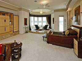 The master bedroom on the ground floor includes a sitting area with panoramic lake views.