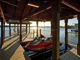 The dock houses a small jet ski and can serve as a location for a romantic dining experience on the lake.