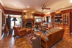 Light streams into the family room with its majestic fireplace through the multiple sets of French doors from the screened veranda with brick arches.
