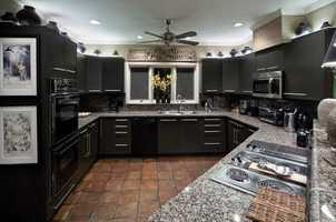 The kitchen features designer cabinetry, stone counters and a professional size refrigerator.