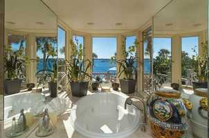 The lavish master bathroom offers a dramatic raised jetted tub with expansive lake views on three sides, a vanity with elegant glass bowl sinks and mosaic-tiled counter.