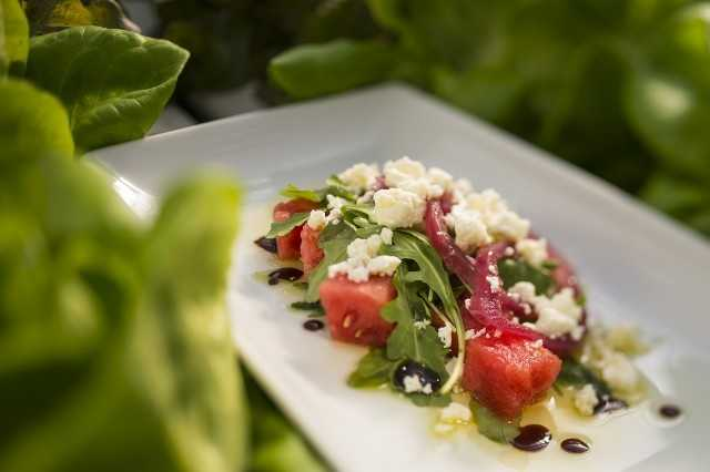 Watermelon salad with pickled onions, BW Farm baby arugula, feta cheese and balsamic reduction is featured at Florida Fresh Outdoor Kitchen.