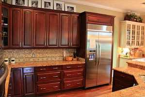 Cherry wood flooring is complimented by darker, cherry wood cabinets in the kitchen. The custom cabinet design is accented by granite countertops, a tile back splash and stainless steel appliances.