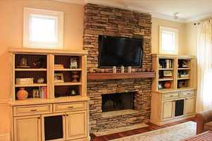 A large TV is mounted above the fireplace in the family room.